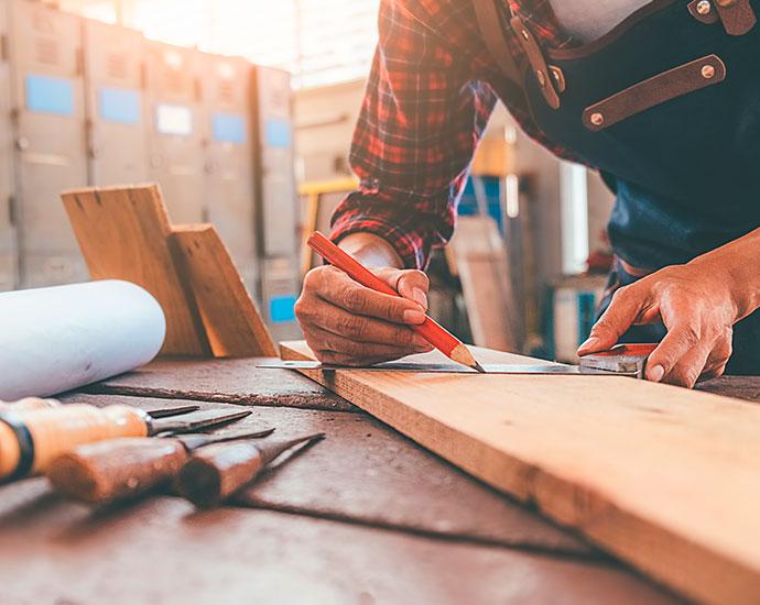 Schreiner mit Bleistift, Winkelmesser und Holz